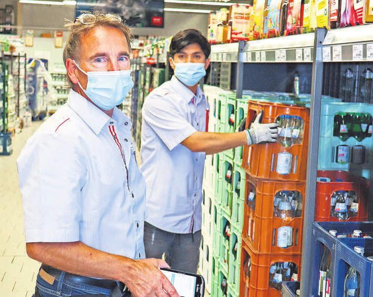 Der stell- vertretende Marktleiter Andreas Schröder (links) und Mitarbeiter Mustafa Gholami beim Bestücken der neuen Lastenregale in der Getränkeabteilung.