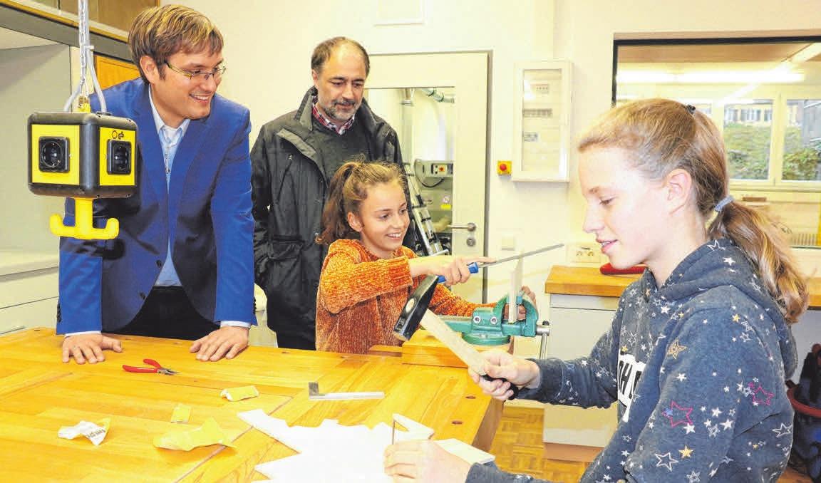 Schulleiter Patrick Maier (li.) und Architekt Odo Jutz schauen den Mädchen über die Schultern. Eine Schülerin arbeitet am Standbohrer.