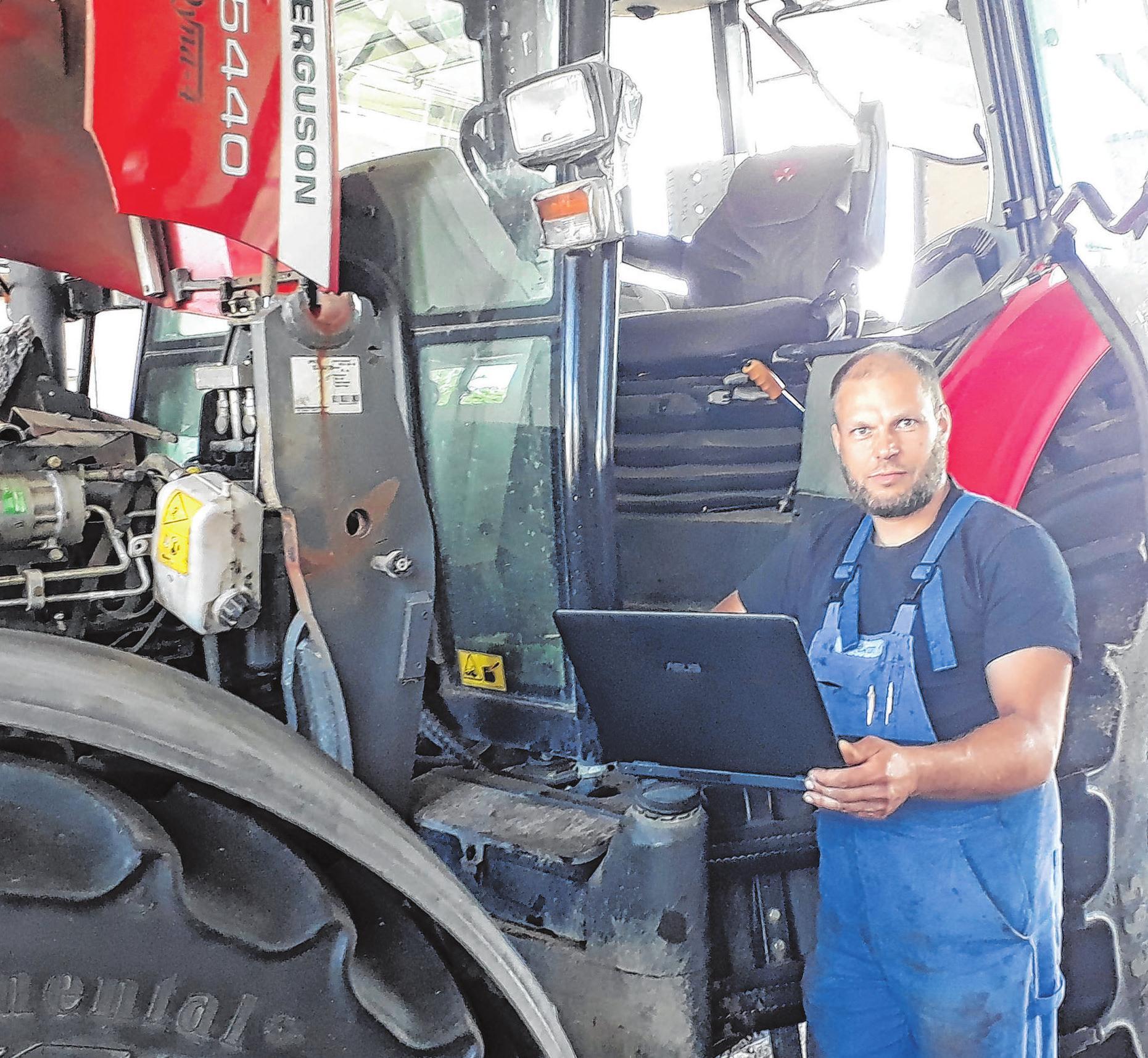Landmaschinenmechaniker René Ewerth am Traktor beim Fehler-Auslesen