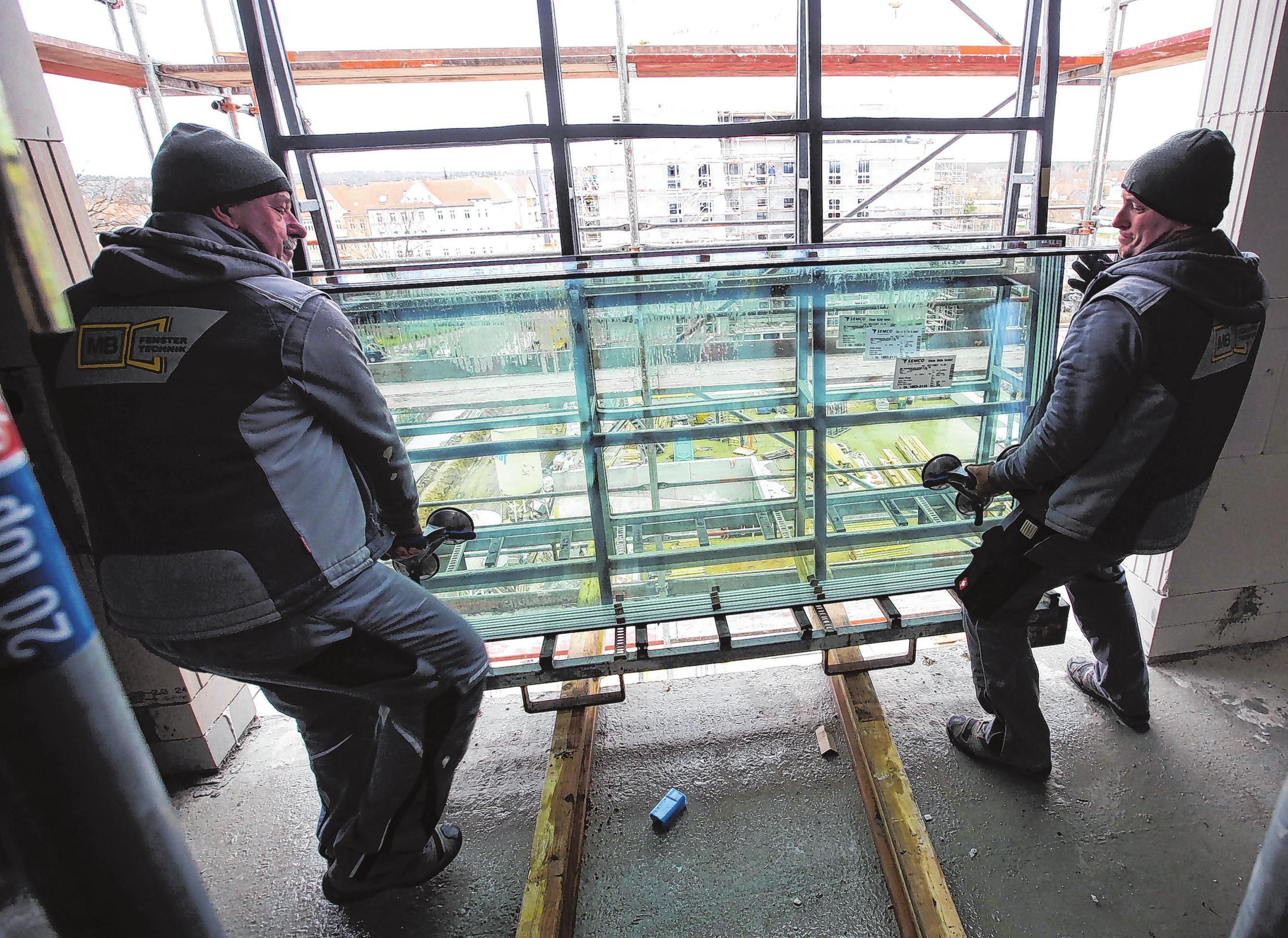 Mitarbeiter der Firma MB Fenstertechnik aus Gransee beim Entladen der dreifach verglasten Scheiben.