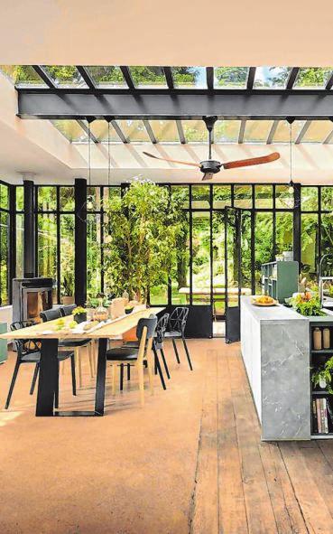 Ein lichtdurchfluteter Traum: eine Kochinsel in Weiß und Beton-Optik inklusive eines integrierten Kräutergartens und im Zentrum die lange Esstafel als Treffpunkt mit der Familie und Freunden.