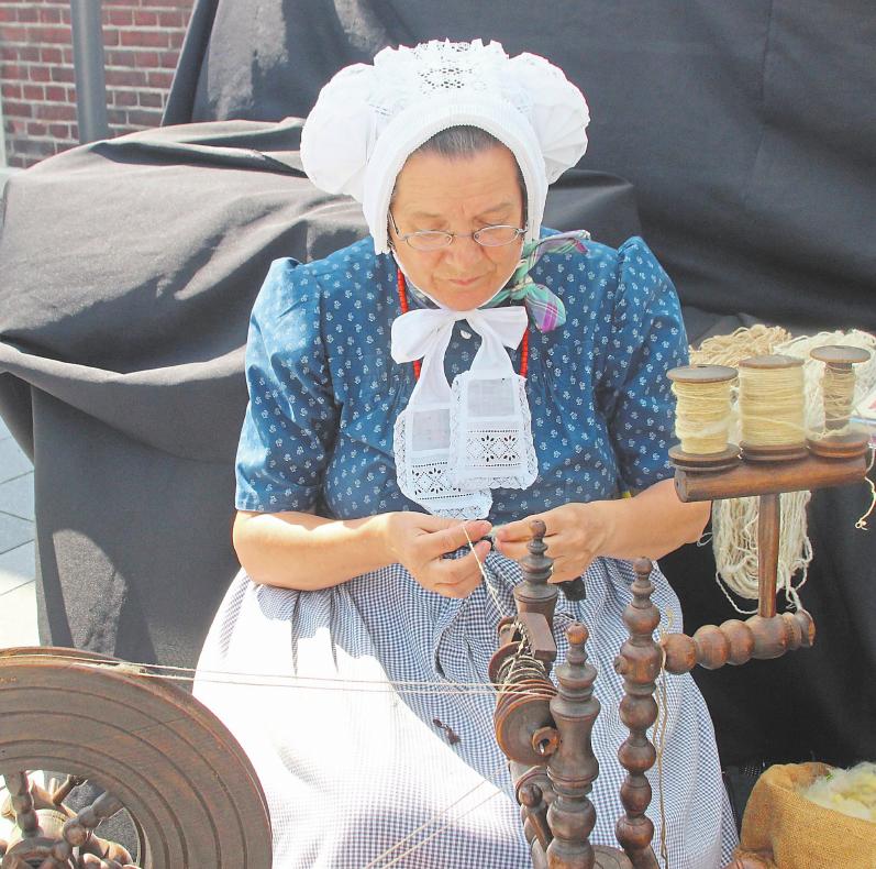 Textilhandwerkskünstlerinnen in alter Tracht spinnen und geben Neugierigen bereitwillig Auskunft.