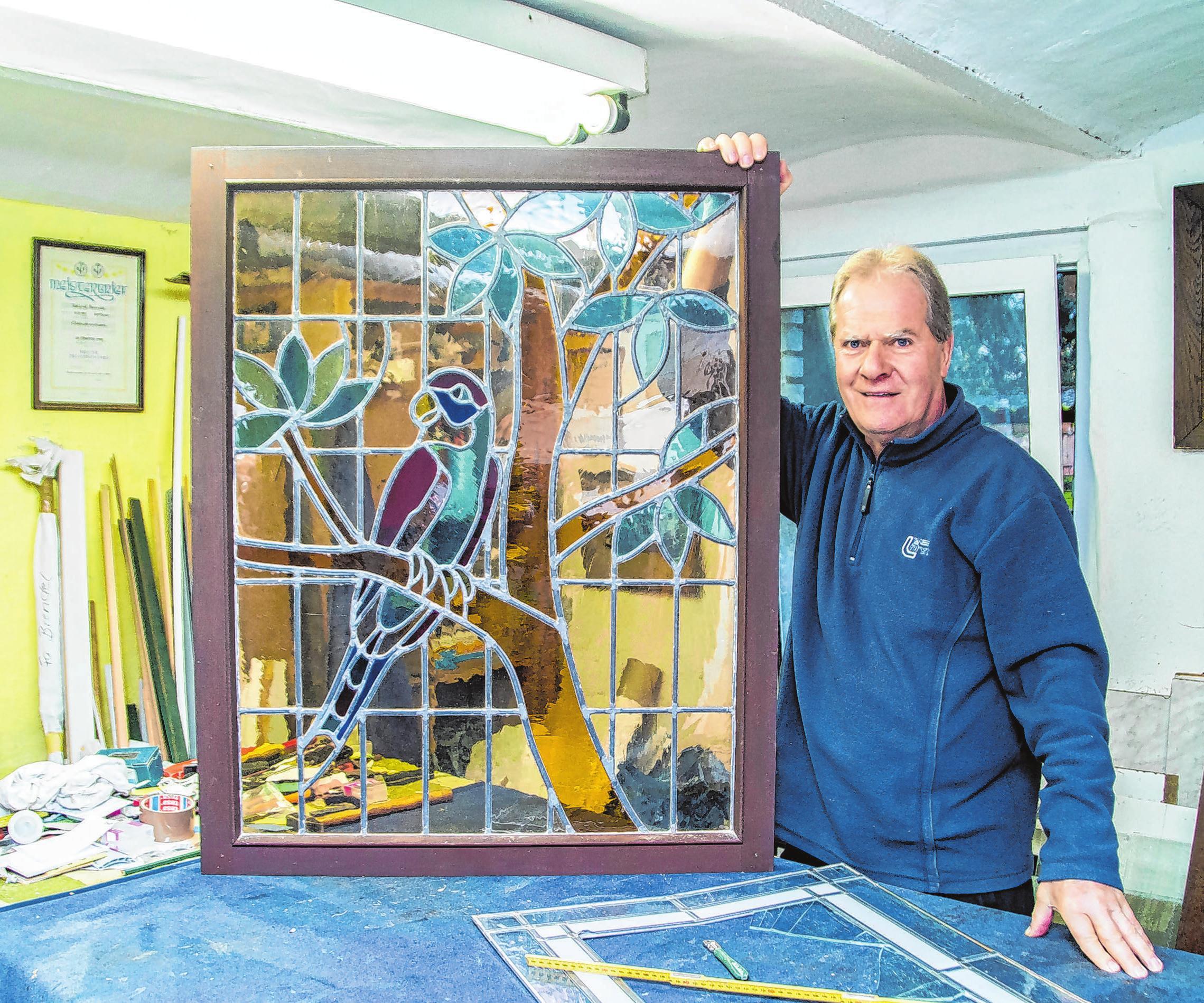 Glasermeister Roland Brendel zeigt eine Bleiverglasung, die zur Reparatur in seiner Werkstatt angekommen ist.