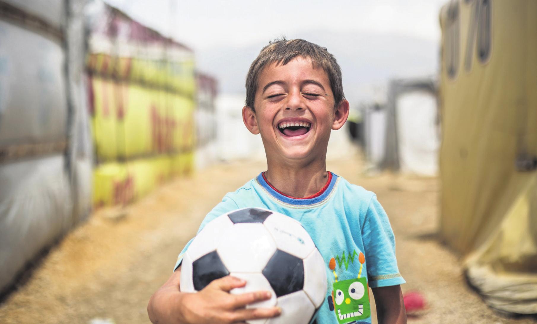 """KIND SEIN DÜRFENDer kleine Othman, geflüchtet aus Syrien, will Fußballspieler werden. """"Ich schieße gerne den Ball, und ich schieße gerne Tore"""", erzählt der Sechsjährige. """"Ich spiele draußen mit meinen Freunden – auch im Regen."""""""