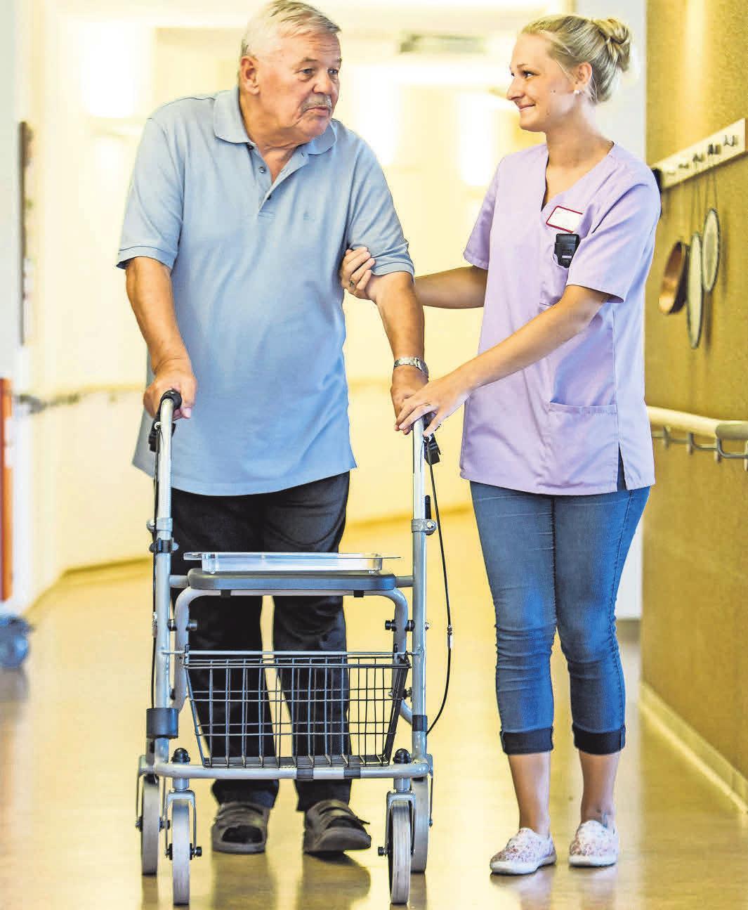 Eine Pflegerin begleitet einen Pflegebedürftigen im Pflegeheim.