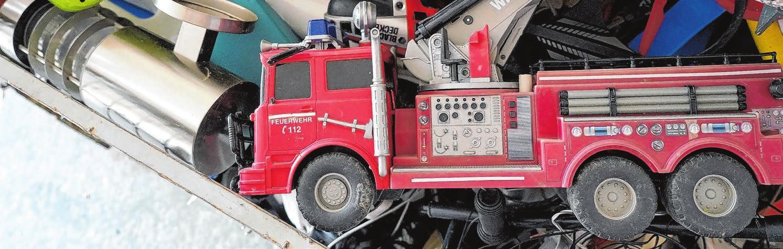 Neben Staubsaugern und Elektrozahnbürsten wartet dieses einst stolze Feuerwehrauto auf sein Ende. Die Metallteile werden entfernt, der rote Kunststoffkörper geschreddert. Foto: Beatrice Schnelle