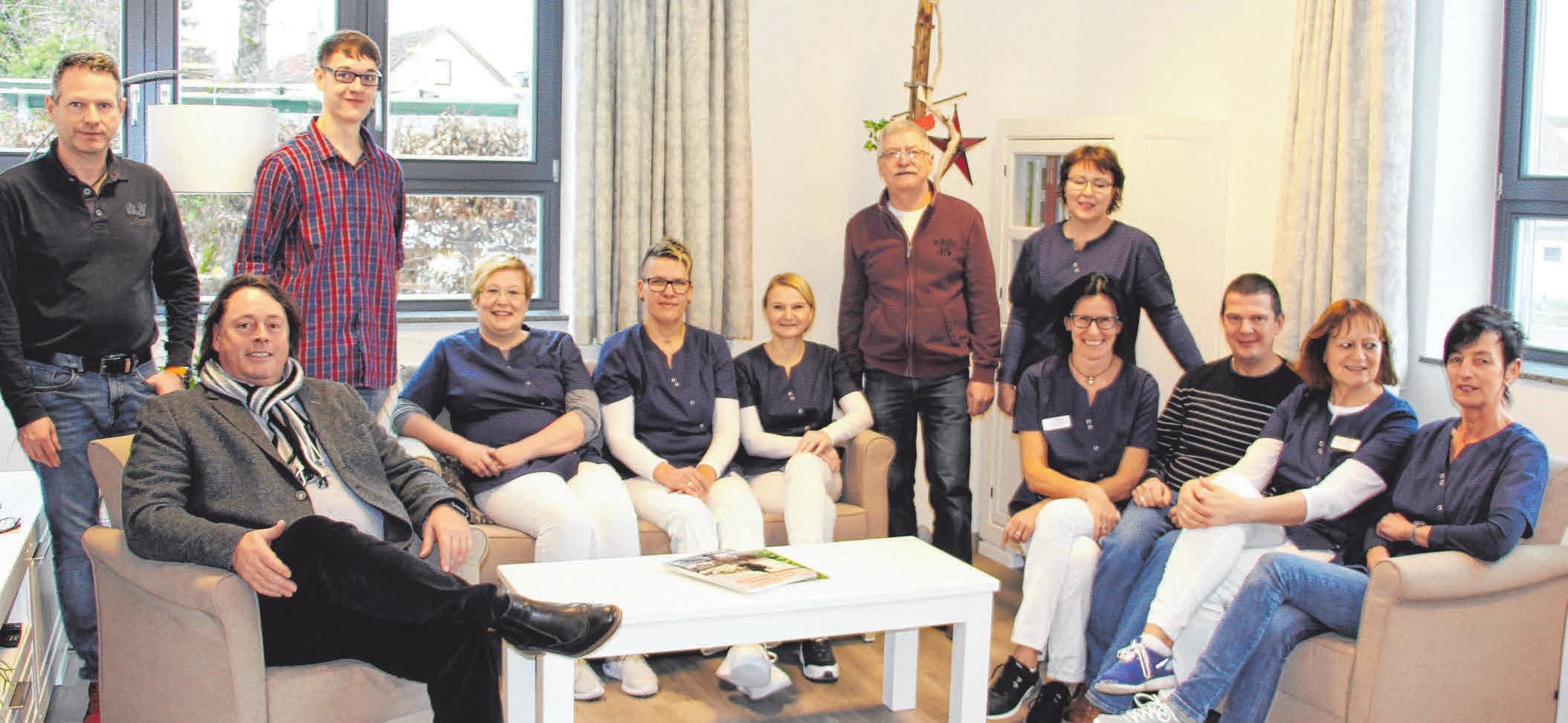 Geschäftsführer Ruldolf Saier (Zweiter von links) und sein motiviertes Tagespflege-Team posieren im Wohnzimmer gut gelaunt für ein Pressefoto. FOTO: SCHMIDL