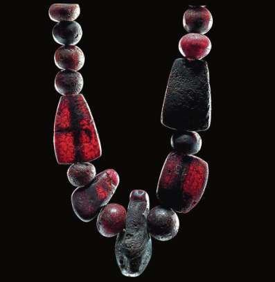 Perlenarmband von Kongehöj, Dänemark. Die Perlen kommen aus Mesopotamien (oben). Teile einer Bernsteinkette aus dem Hortfund Dieskau II, Saalekreis, Sachsen-Anhalt.