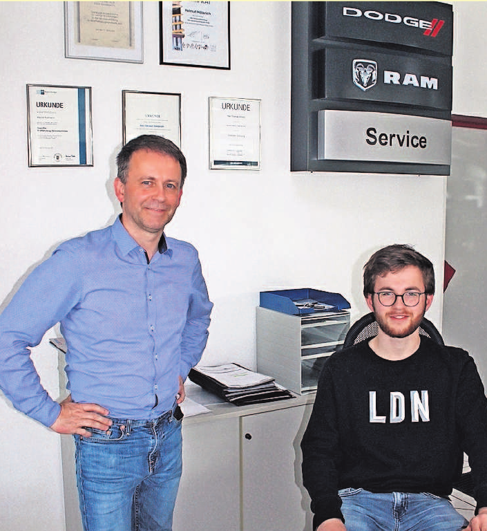 Vor dem Schild der Vertragspartner Dodge und RAM arbeiten im Büro und beraten die Kunden: John Höllerich (rechts), der derzeit eine Ausbildung zum Automobilkaufmann absolviert, und Firmengründer Helmut K. Höllerich. Foto: wb