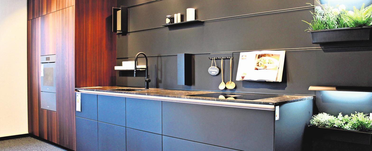 Eines von vielen Küchenbeispielen im Küchenhaus Basler: Küche in Fenix onyxschwarz/ Lärche und Steinarbeitsplatte