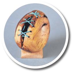 Ein aufgebrochenes Ei aus Holz, das mit einer Naht zusammengehalten wird.FOTO: SCHILLING