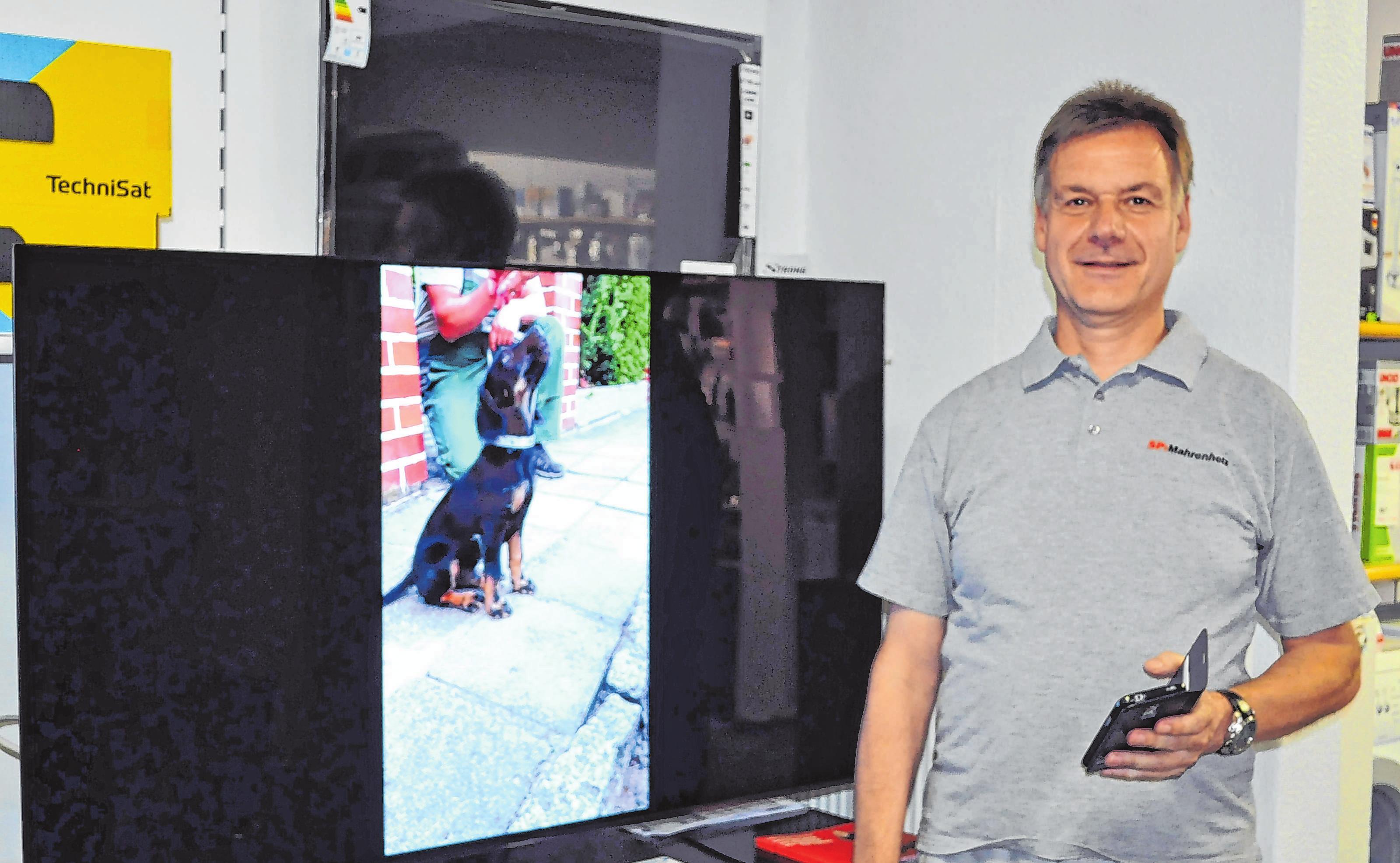 In Seelow in der Frankfurter Straße 59: Dirk Mahrenholz führt vor, wie die Übertragung von Handyfotos auf ein Fernsehdisplay funktioniert. Fotos: Cornelia Mikat