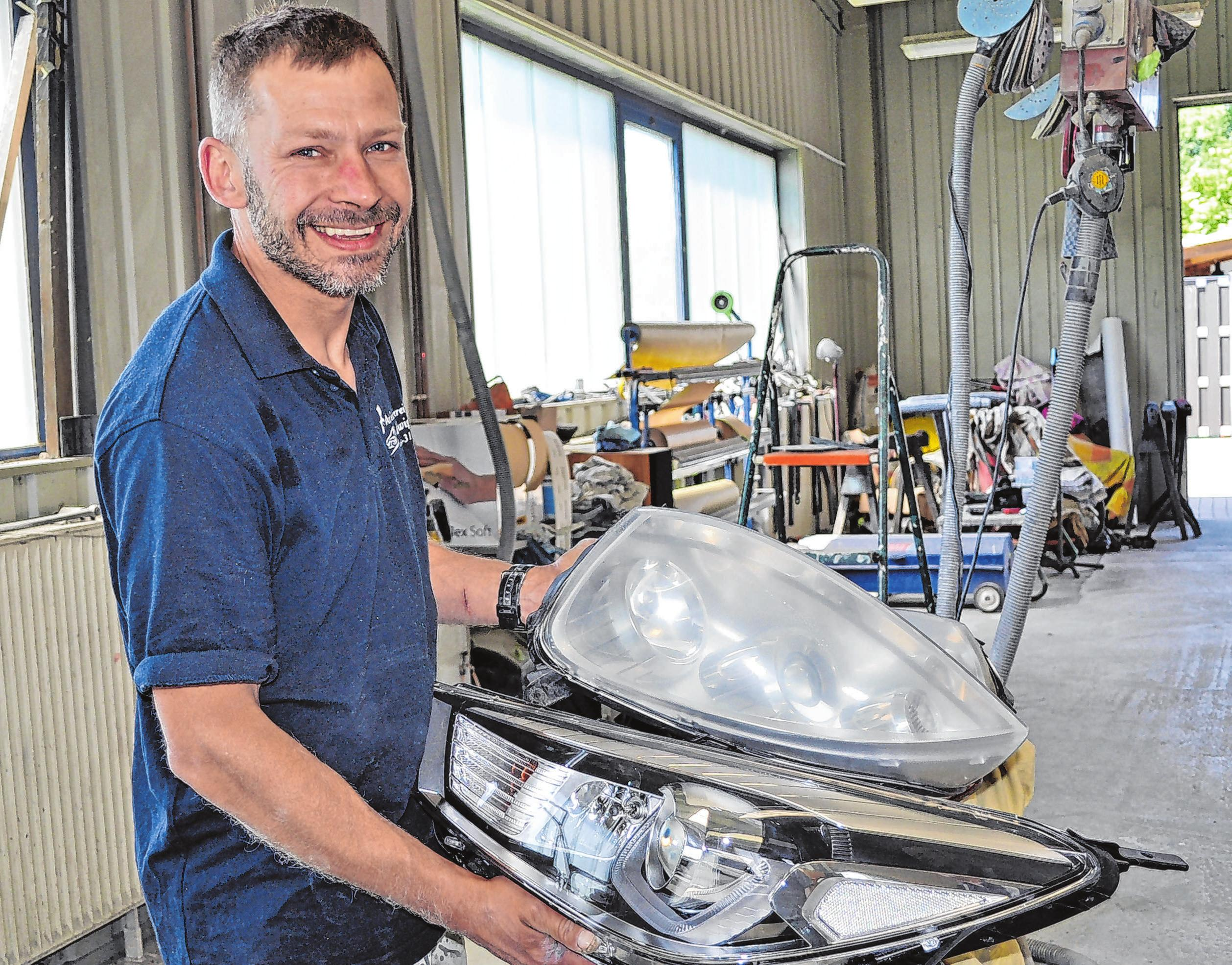 Mitarbeiter Krzysztof Gonisiewski demonstriert, wie gut reparierte alte Scheinwerfer nach der Spezialbehandlung in der Werkstatt wieder aussehen.