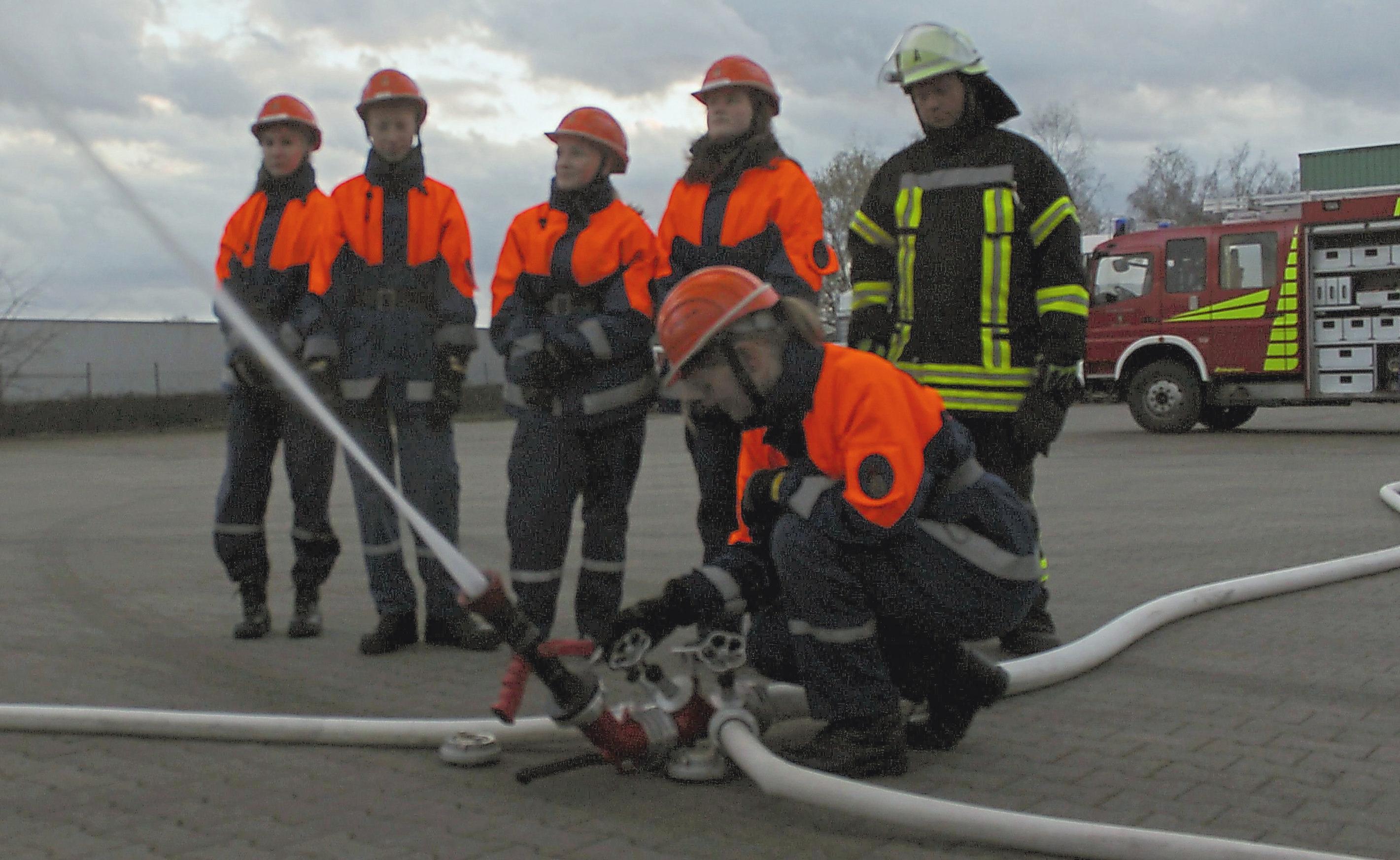 Mit zwei Druckschläuchen und einem Verteiler bauen die Mitglieder der Jugendfeuerwehr einen improvisierten Wasserwerfer. Die Übung ist Teil der Jugendflamme II.