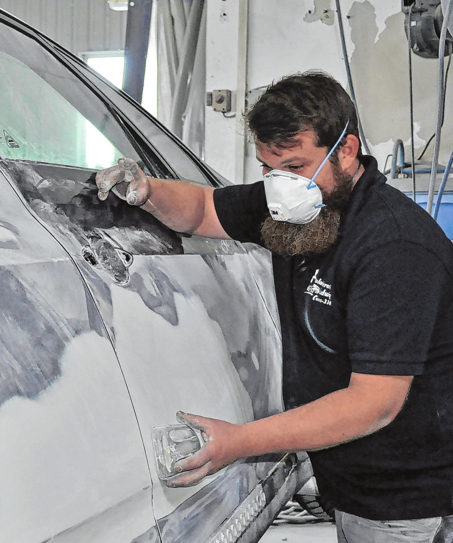 Vorbereitung für das Lackieren: Stephan Ludwig beim Schleifen einer Autotür