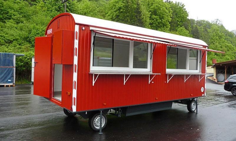 Leuchtend rot lackiert lockt dieser Verkaufsbauwagen mit Gerätekasten und Verkaufsklappen in der Gemeinde Sulzfeld die Kunden an.