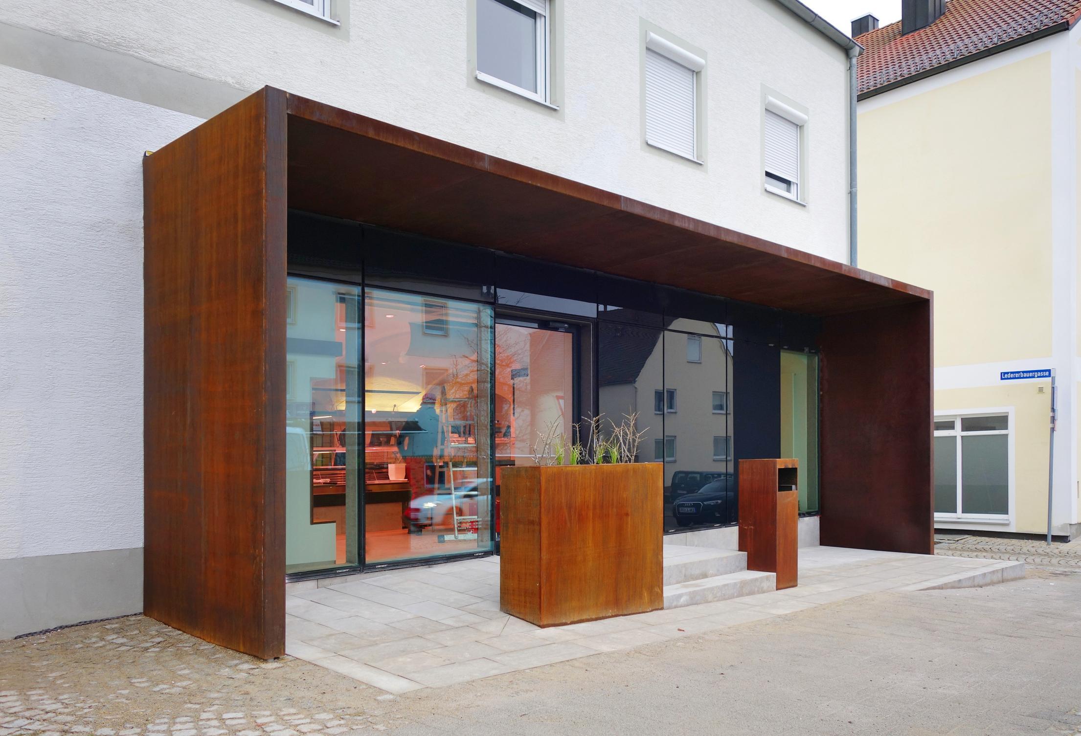 Die Filiale der Metzgerei Pauleser im neuen Design: Der Eingangsbereich erinnert mit seiner Cor-Ten-Stahl-Konstruktion an die Köschinger Tore im Kreisverkehr am nordwestlichen Ortseingang. Die große Glasfront lässt viel Licht ins Innere fluten.