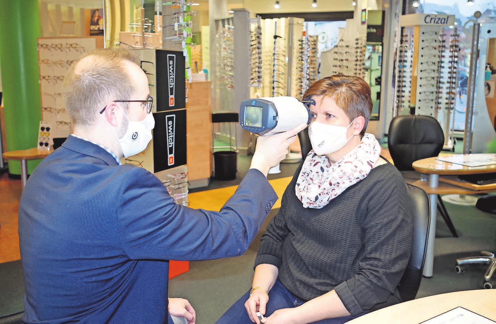 Steffen Heitmann misst mit dem Handy-Ref die Brillenwerte.
