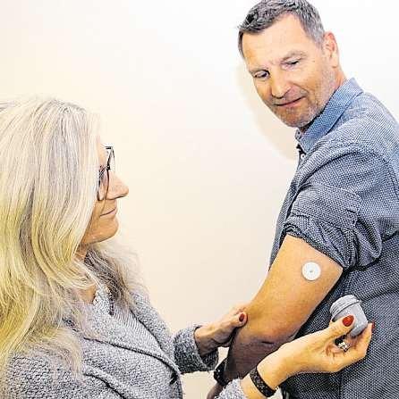 Kleiner Pieks: Andrea Lamp bringt den Blutzucker-Sensor an Detlef Landts Oberarm an.FOTO: TESSA MAIBORG