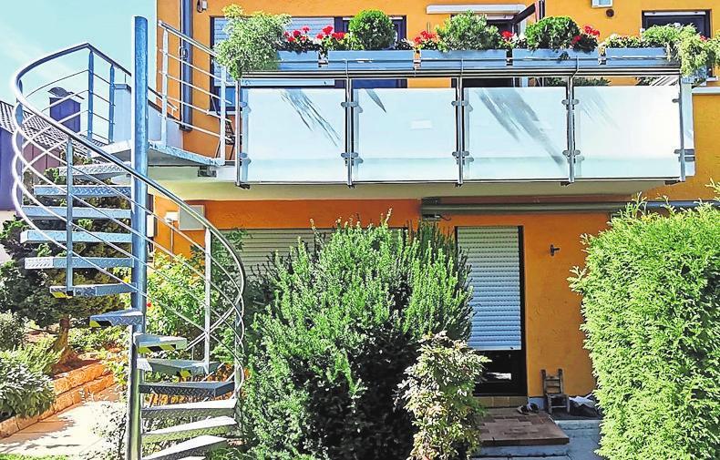Die elegante Spindeltreppe verbindet Balkon und Garten.