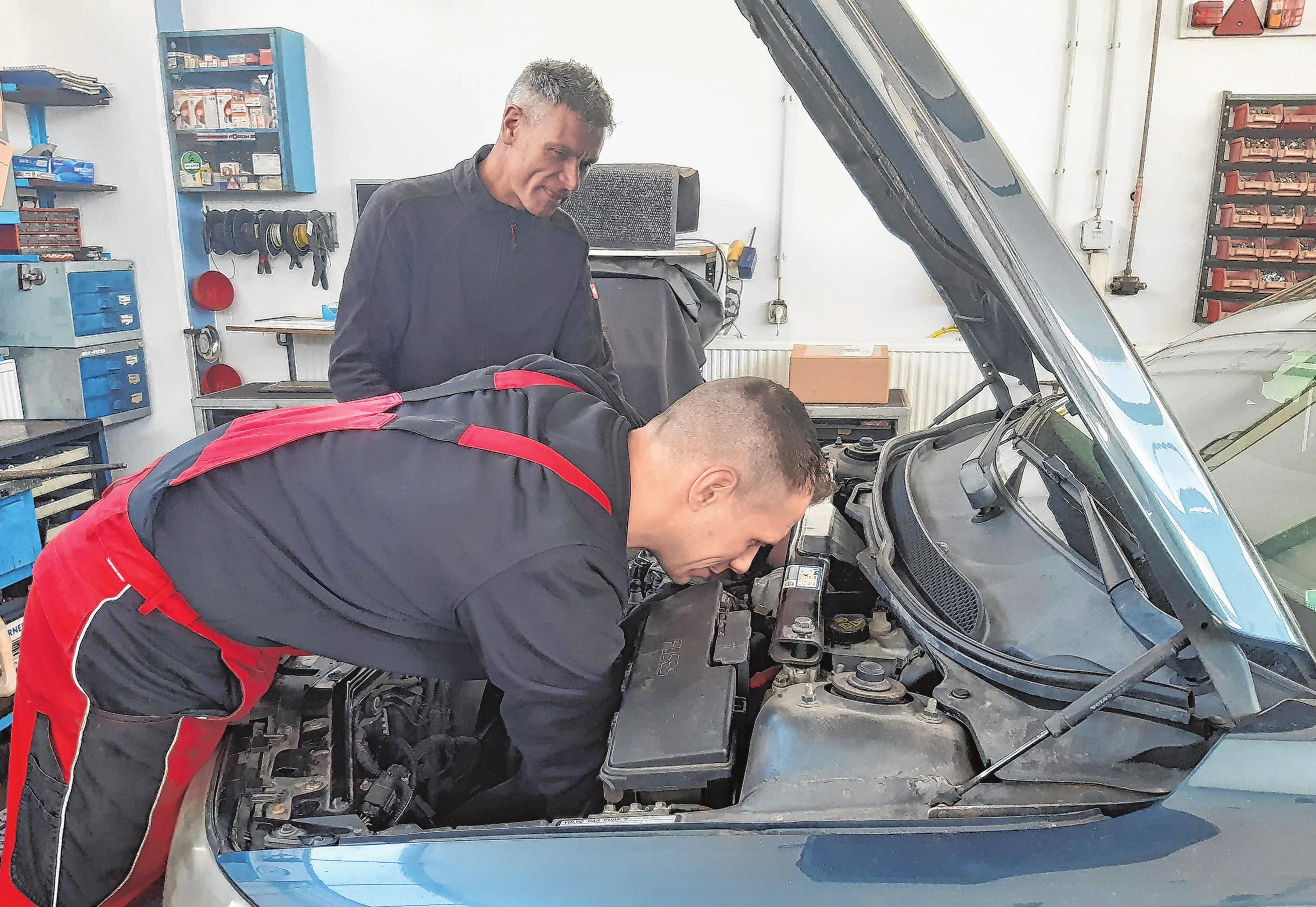 Gemeinsamer Fahrzeugcheck: Firmenchef Uwe Rätz und Kfz-Meister Christopher Dollase bei der Motorinspektion an einem Auto.