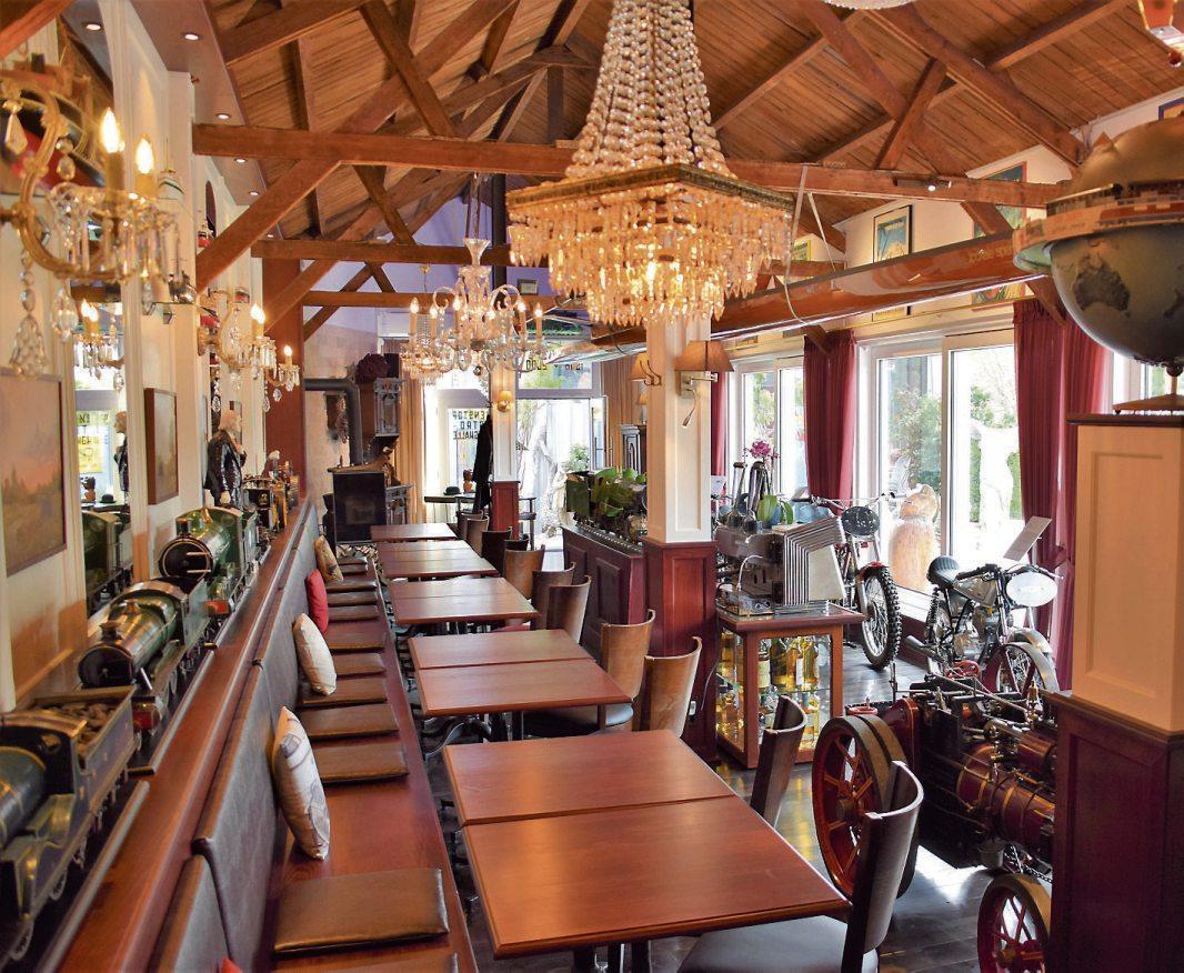 """Ganz links: Die neu gestaltete """"Büssinghalle"""", in der man seit heute fein à la carte essen kann – umgeben von historischen Exponaten und einem schönen Blick auf die """"AmmerTerrasse""""."""