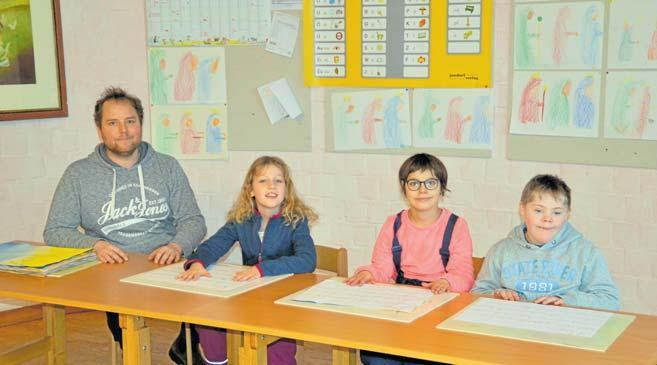 Die dritte Klasse behandelt den Schöpfungsbericht. Heilpädagoge Christopher Winkelmann (v.li.n.re.) und seine Schüler Emilia (9), Amelie (10) und Mika (9) sind stolz auf ihre zum Thema passenden Schreibübungen. FOTO: REG