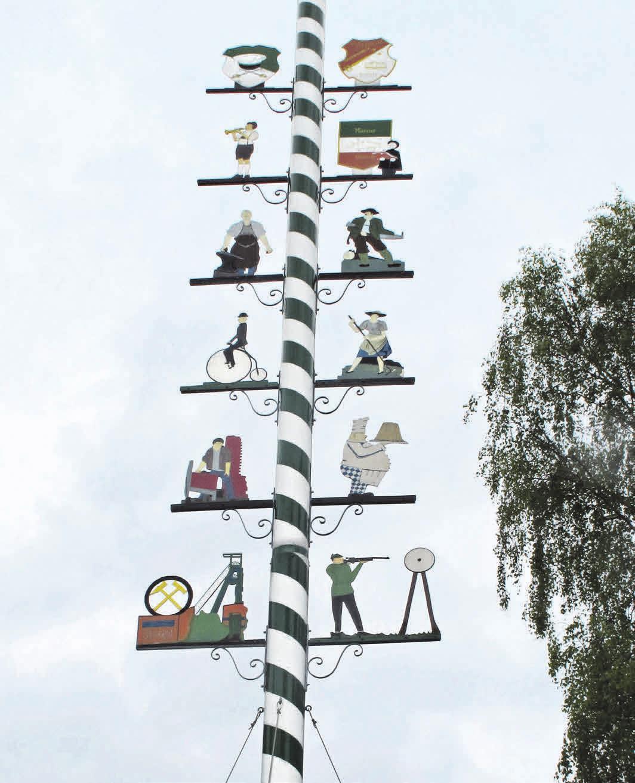 Der Vöhrumer Maibaum ist mit den Emblemen unterschiedlicher Handwerkszweige und Vereine geschmückt.