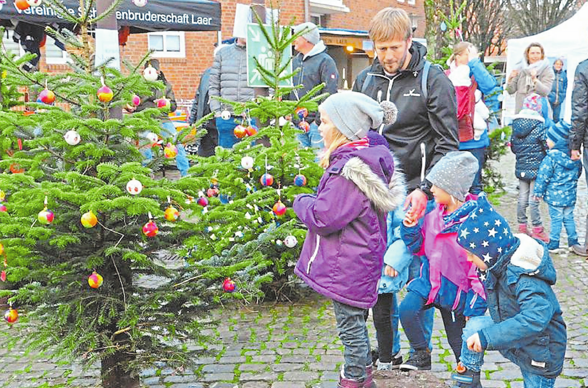 Schon die jüngsten Laerer beteiligen sich an ihrem Weihnachtsmarkt: Sie schmücken die Tannenbäume im Ortskern. Foto: Rainer Nix