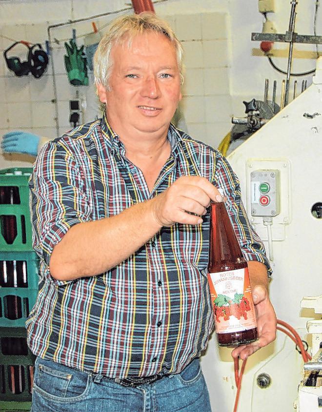Inhaber Martin Schmidt an der Abfüllanlage, in der gerade roter Johannisbeer-Nektar in Flaschen abgefüllt wird Foto: cs