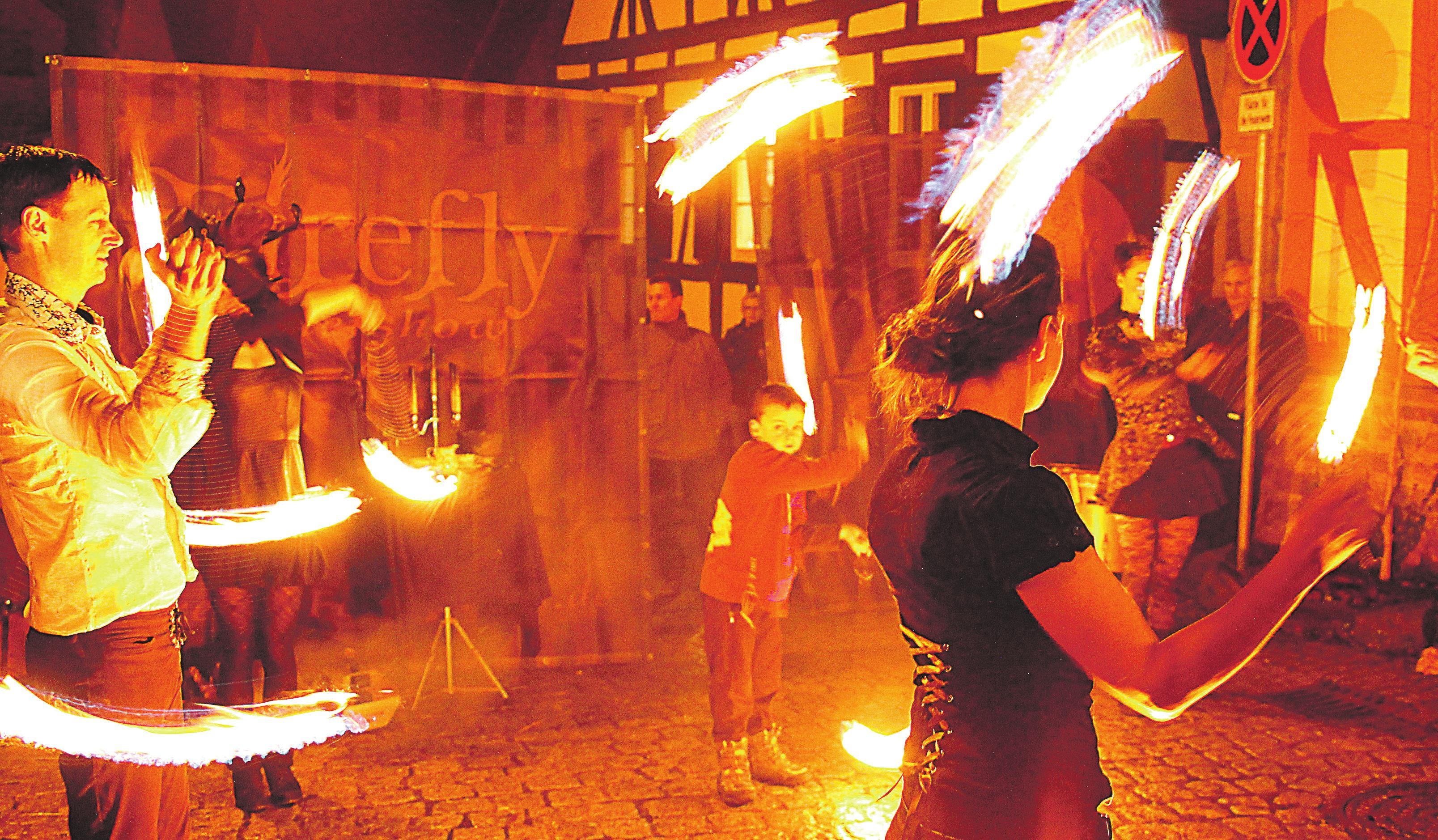 """Eine der mittelalterlichen Jahrmarktsattrationen nach Einbruch der Dunkelheit: eine rasante Feuershow mit der einheimischen Truppe """"Firefly""""."""