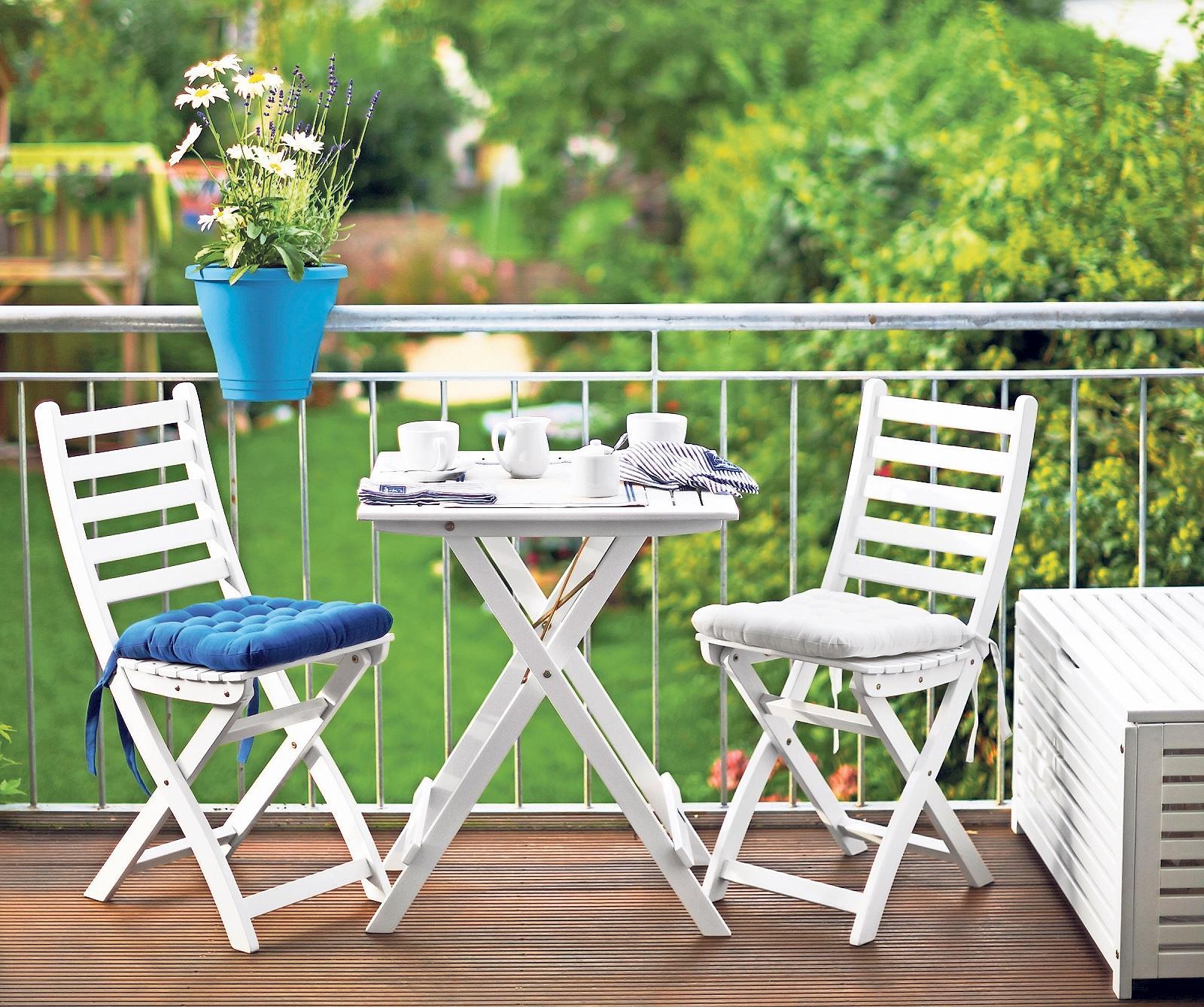 Blau macht als Akzentfarbe auf dem Balkon viel her: Es setzt sich von den dezenteren Farben für Möbel und Boden ab und harmoniert mit dem Grün der Bepflanzung. Foto: Butlers/dpa-tmn