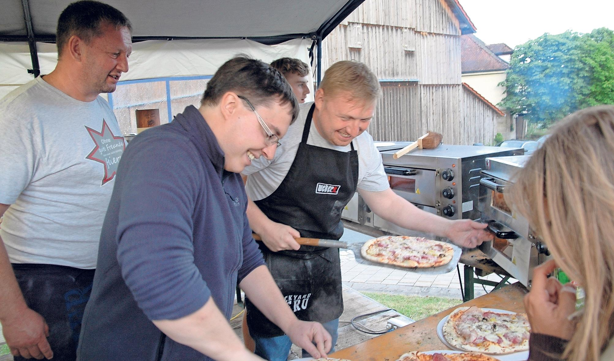 Beim Pizzabacken mit Bäckermeister Florian Pausch (mit Schürze) ist auch Pfarrer Michael Braun (vorne) als Helfer im Einsatz.