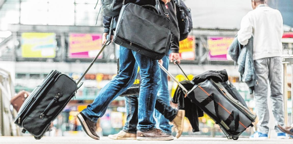 Reisende mit Gepäck am Hauptbahnhof in Hamburg. FOTO: MARKUS SCHOLZ, DPA