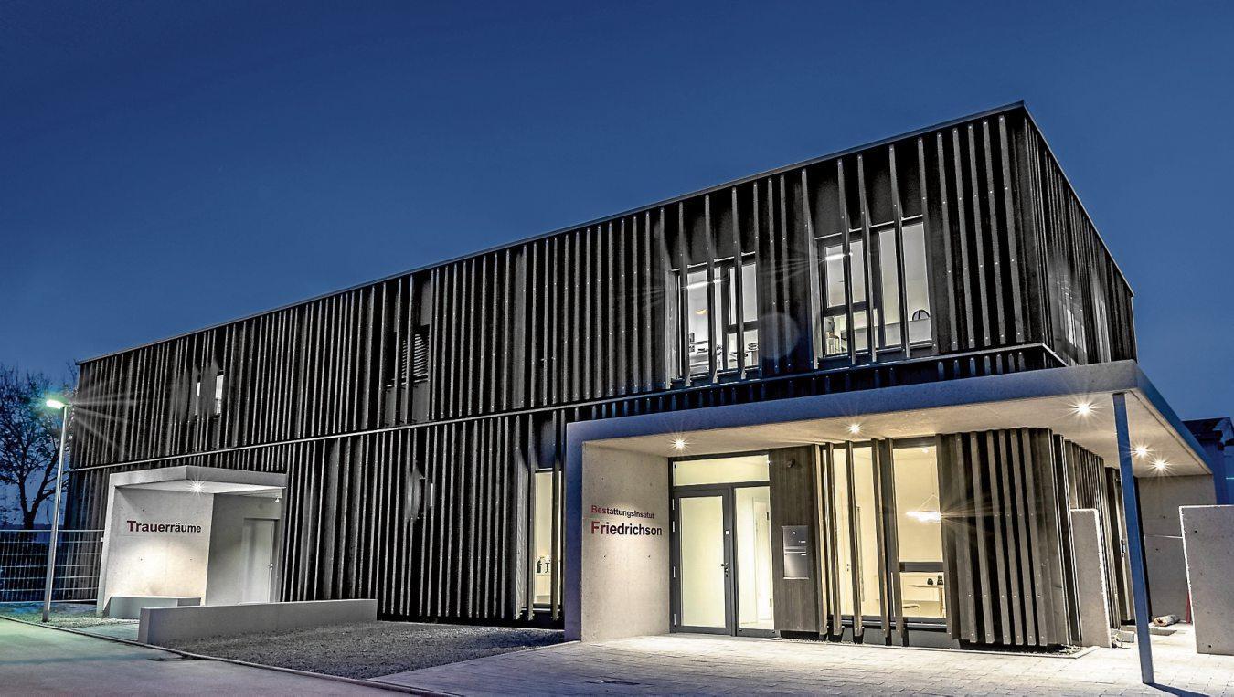 Der Neubau von Bestattungsinstitut Friedrichson besticht mit seiner Holzlamellen-Fassade. Im oberen Stockwerk sind die Büroräume untergebracht.