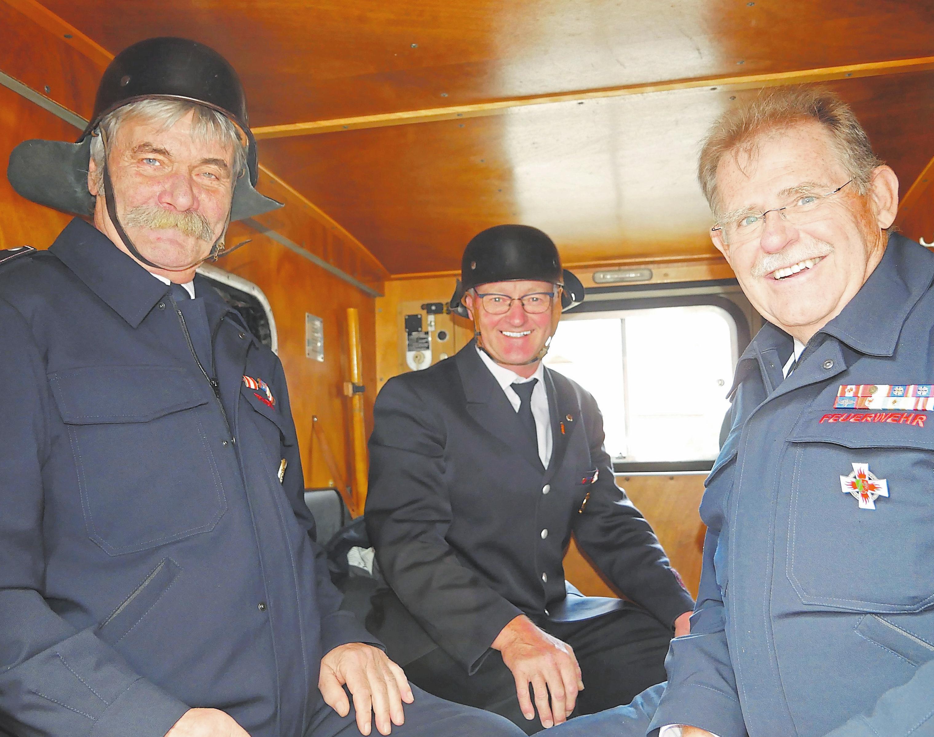 Fast wie vor 50 Jahren: Franz-Peter Datema, Herbert Sievers und Reinhard Seebröker nehmen im historischen Feuerwehrauto Platz. Foto: Christiane Husmann