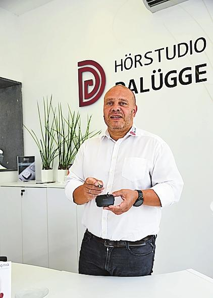 Geschäftsführer Axel Dalügge zeigt ein filigranes Hörgerät mit Ladestation. FOTO: KÖN