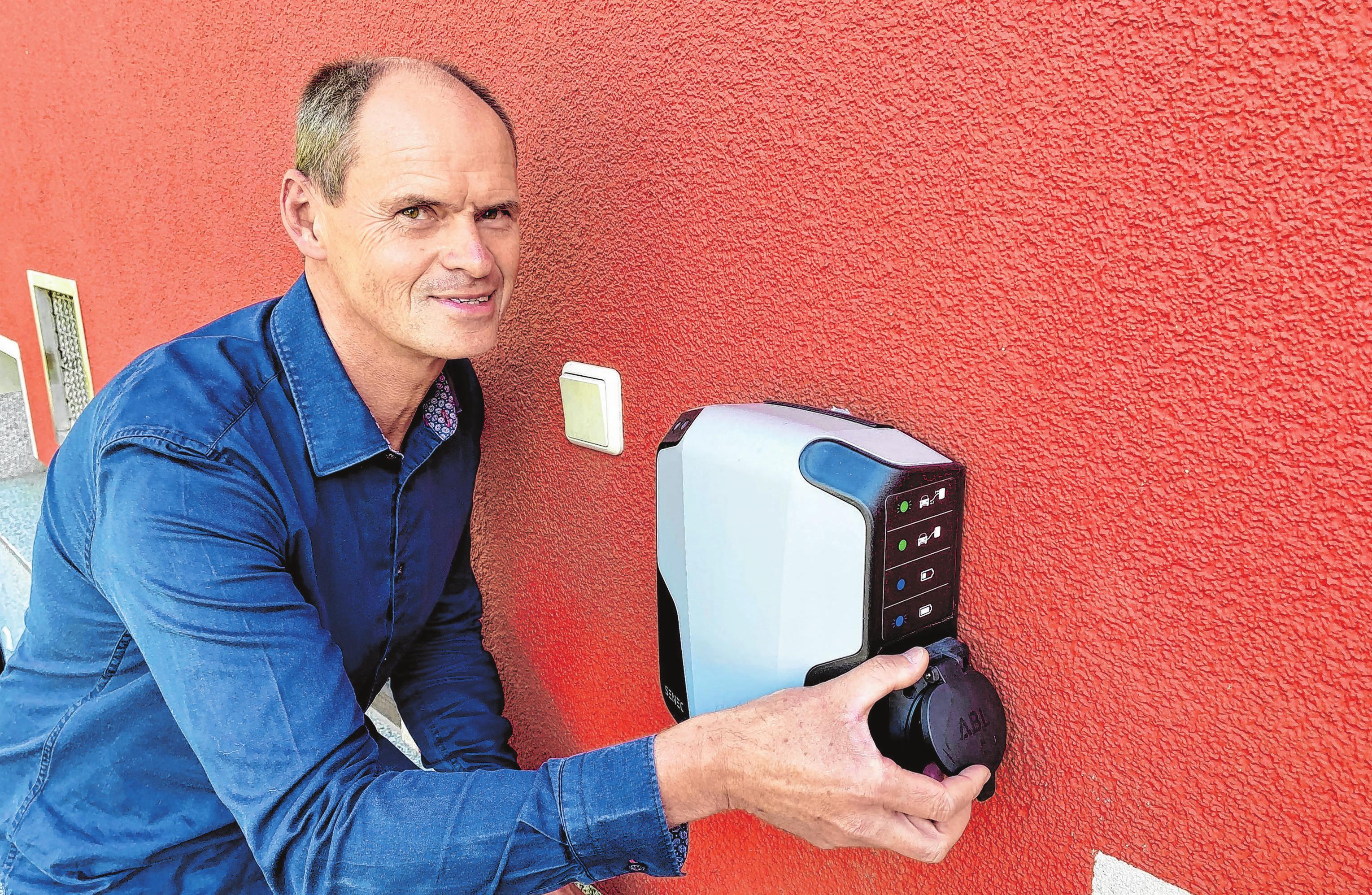"""Rene Pötzsch von den """"Haushandwerkern"""" zeigt eine Wallbox an der Hauswand. Die Zapfstelle für ein E-Auto wird einfach mit einen LAN- und einem Stromkabel mit dem Speicher verbunden. Fotos: Alexander Winkler"""