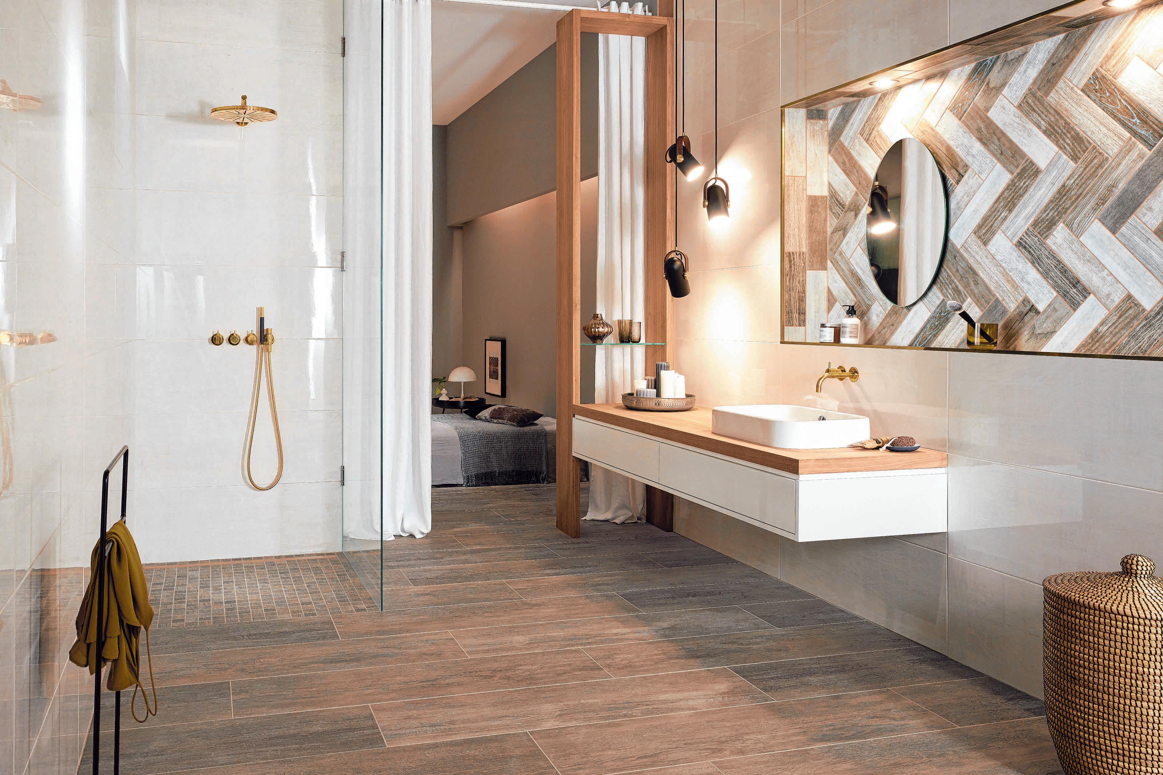 Die durchgängige Bodengestaltung von Bad und Duschbereich mit robusten Feinsteinzeug-Bodenfliesen in angesagter Holzoptik vergrößert den Raum optisch.