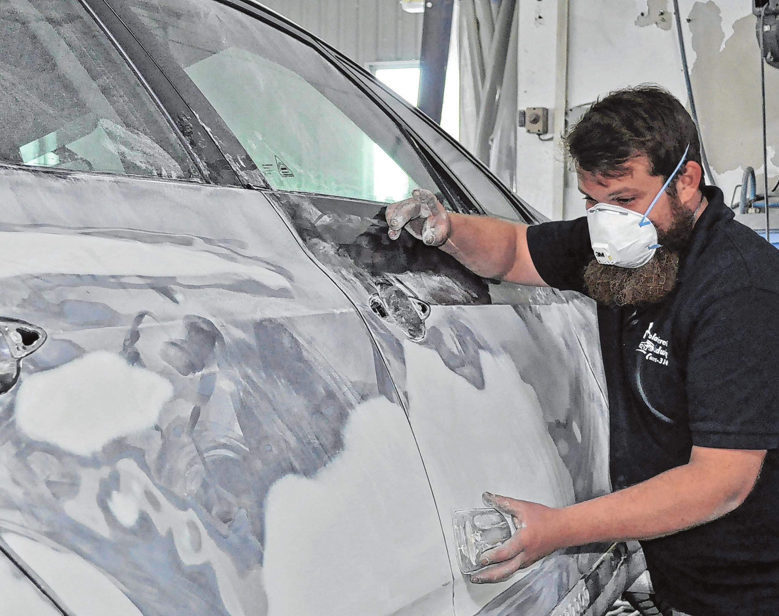 Vorbereitung für das Lackieren: Stephan Ludwig beim Schleifen einer Autotür.