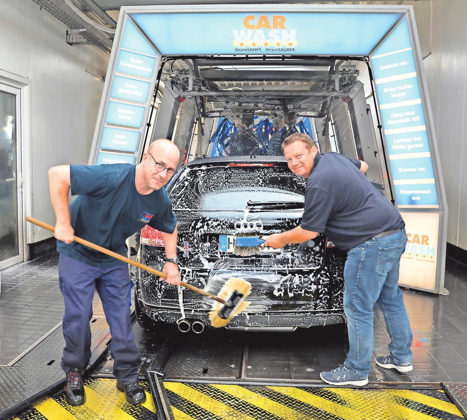 CAR-WASH-Chef Carsten Mölich (rechts) und Mitarbeiter René Schmidt bei der Vorreinigung mit Warmwasser, das aus der Abwärme des firmeneigenen Blockheizkraftwerkes gewonnen wird.