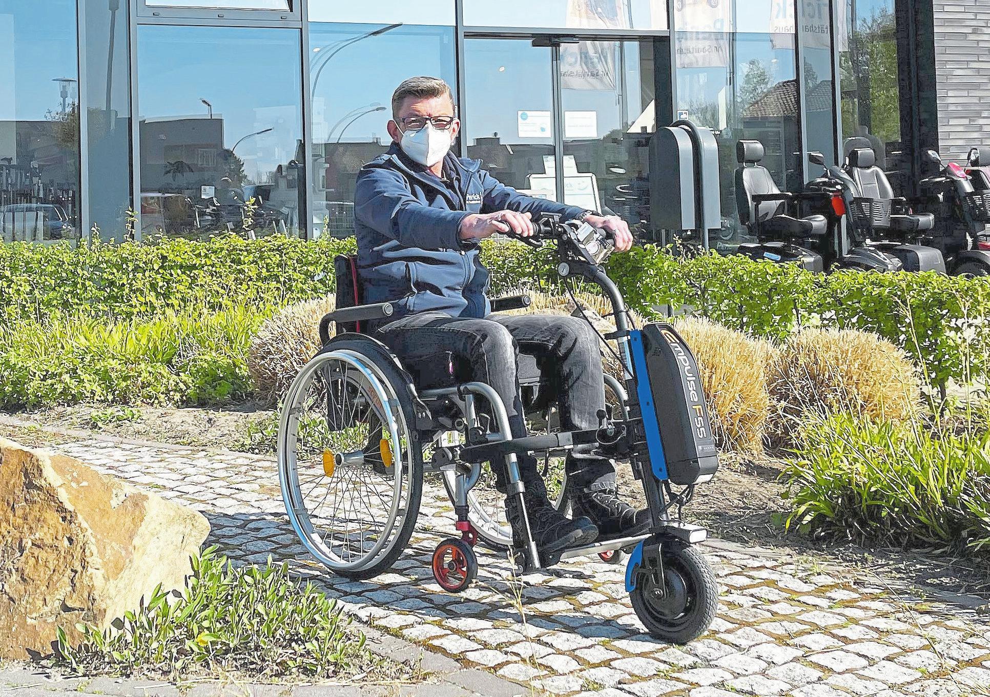 Perick-Mitarbeiter Andreas Bente demonstriert das Zuggerät Empulse F55, das vor einem Rollstuhl adaptiert ist.