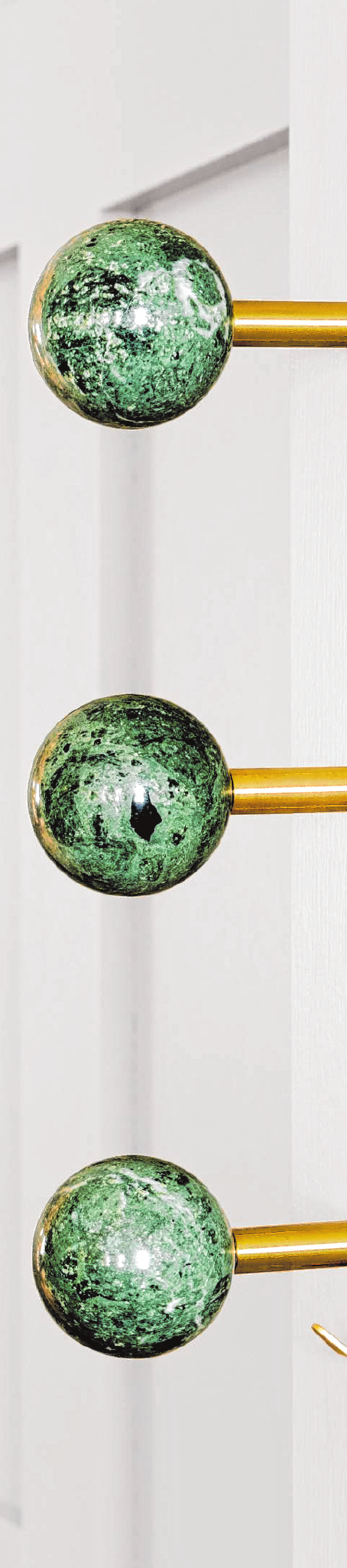 Einzelne Kugeln aus Marmor an einer Edelstahlstange: Die Dots Stone der Firma Schönbuch sind als Raumdeko gedacht, doch funktionieren auch als Kleiderhaken.