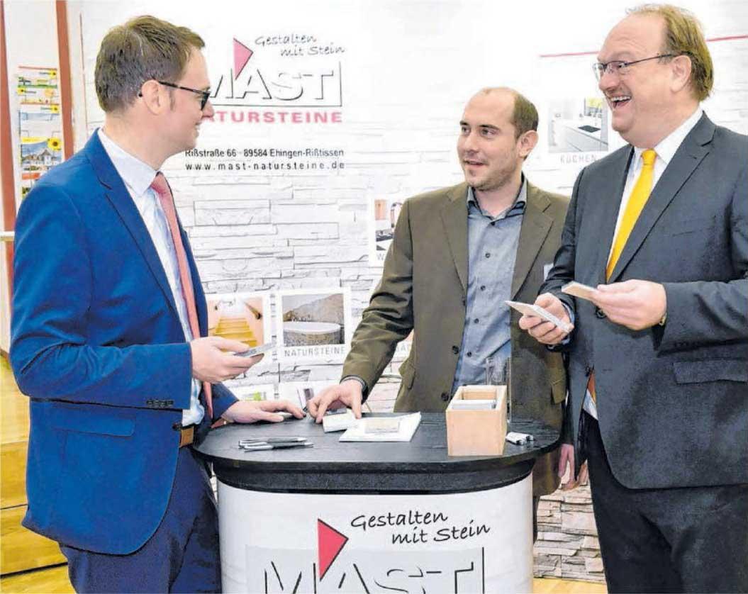 Vorstandssprecher Jost Grimm von der Donau-Iller Bank und Bürgermeister Sebastian Wolf informieren sich bei Peter Mast vom Steinmetzbetrieb Mast aus Rißtissen.