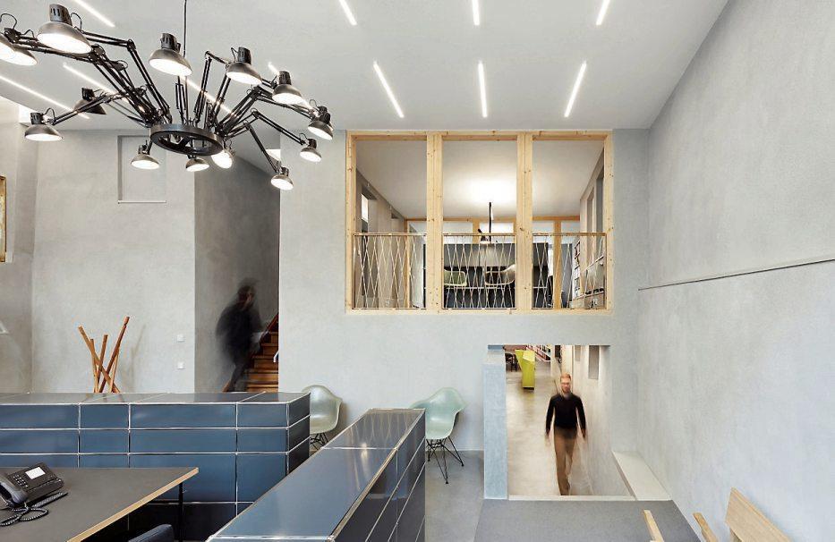 Der Empfangsraum ist umgeben von Treppen: an der Decke hängt ein riesiger Kronleuchter aus Schreibtischlampen.