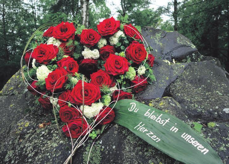 Ein aus roten Rosen geschmückter Kranz in Herzform ist ein schöner Ausdruck der Erinnerung. Foto: Deutsche Friedhofsgesellschaft/akz-o
