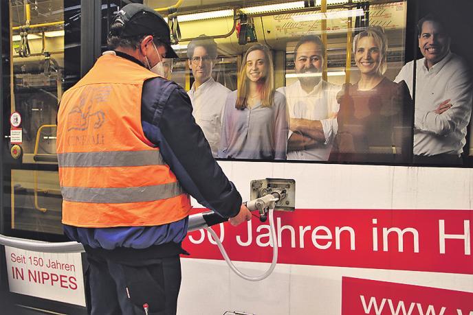 Ein Mitarbeiter lässt Bremssand in eine Stadtbahn ein