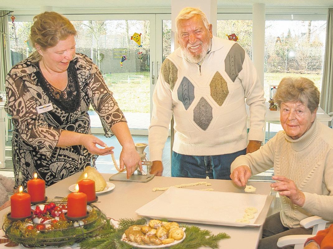 Betreuungskraft Jeanette Vogt und Hannes-Siegfried Czernitzki drehen den Teig durch die Plätzchenmühle. Fotos: Umsorgt Wohnen