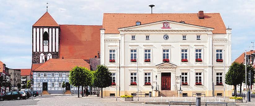 Das Rathaus und dahinter die Kirche St. Peter&Paul prägen das Stadtbild von Wusterhausen. Foto: Gemeinde Wusterhausen